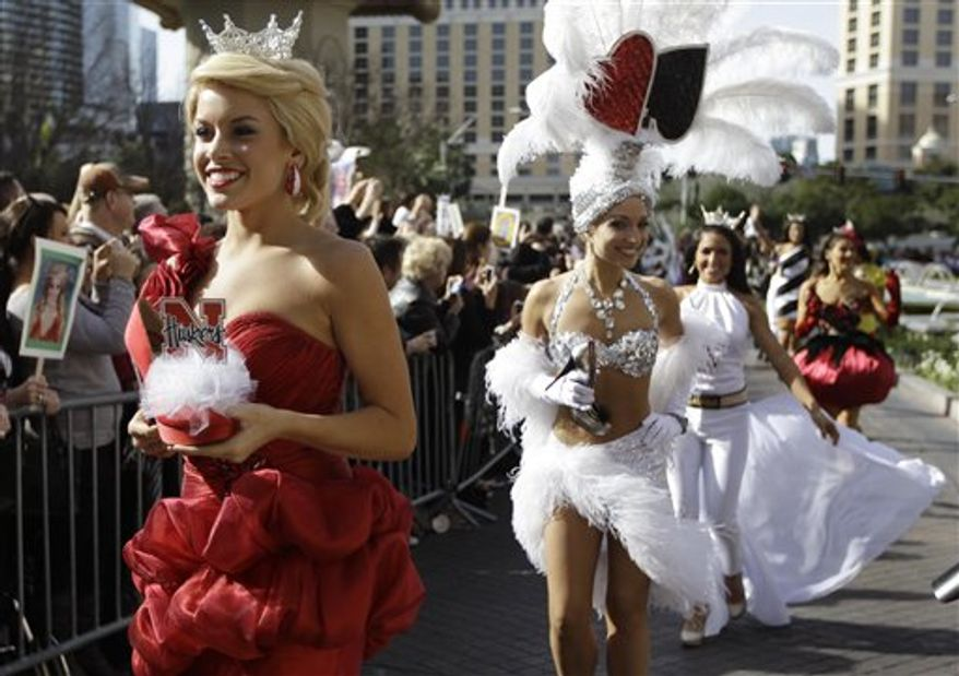 """Miss Nebraska, Teresa Scanlan, left, followed by Miss Nevada Cris Crotz and Miss New Hampshire, Krystal Lee Muccioli walk in the """"Show Us Your Shoes"""" parade as part of this week's Miss America festivities Friday, Jan. 14, 2011 in Las Vegas. (AP Photo/Julie Jacobson)"""