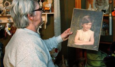 "Janice McKinney places a portrait of her daughter, Cherrie Mahan, that was made a few years before the 8-year-old went missing back in 1985, back onto the cabinet where she keeps it in her home in Saxonburg, Pa. State police say someone has provided ""potentially crucial"" information that could help them solve the case of the Pennsylvania girl missing for almost 26 years. (Associated Press)"