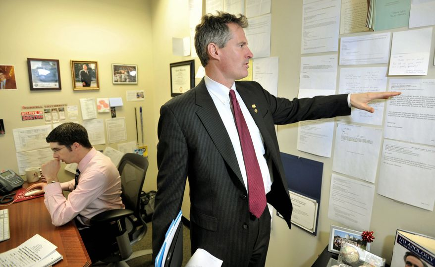 """Sen. Scott Brown looks at thank-you notes affixed to a wall in his Boston office from constituents that his office had assisted. Austin Lord (left) is Mr. Brown's constituent-service official. """"You need to make sure that you move the country forward,"""" Mr. Brown said. (Associated Press)"""