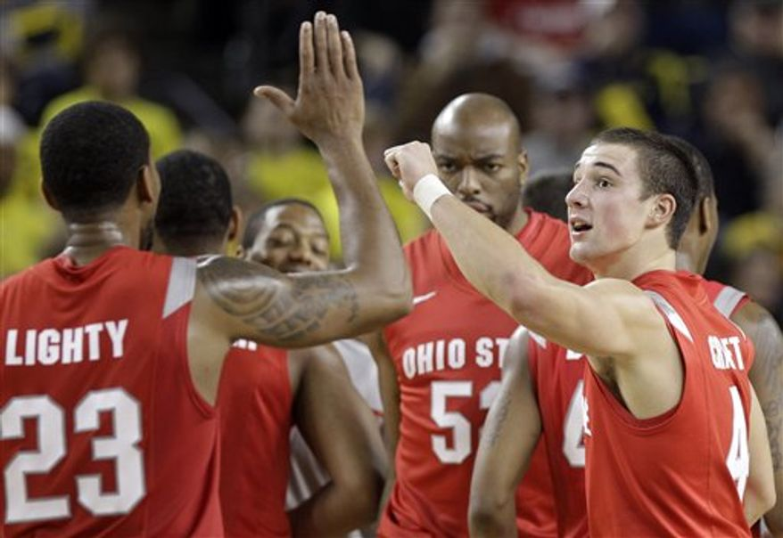 Ohio State forward David Lighty, left, shoots over the defense of Michigan forward Evan Smotrycz (23) during the first half of an NCAA college basketball game in Ann Arbor, Mich., Wednesday, Jan. 12, 2011. (AP Photo/Carlos Osorio)