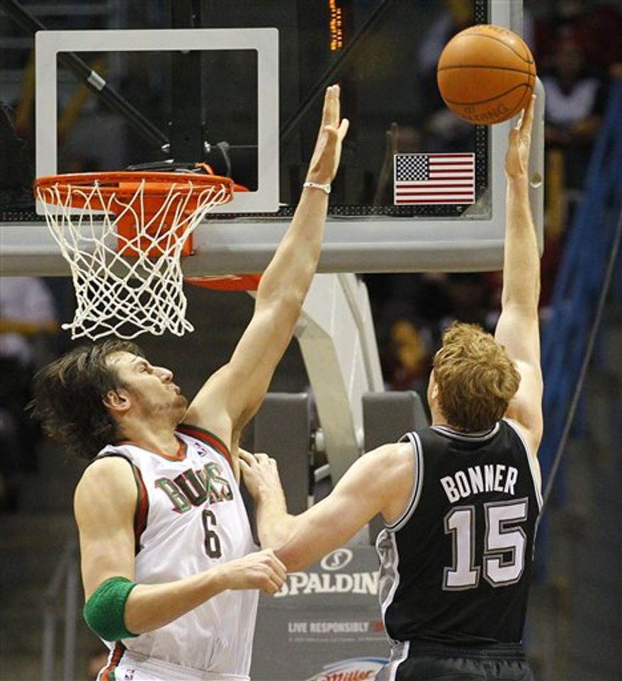 San Antonio Spurs' Matt Bonner(15) puts up a shot against Milwaukee Bucks' Andrew Bogut(6)  in the second half of an NBA basketball game Wednesday, Jan, 12, 2011, in Milwaukee. (AP Photo/Jeffrey Phelps)