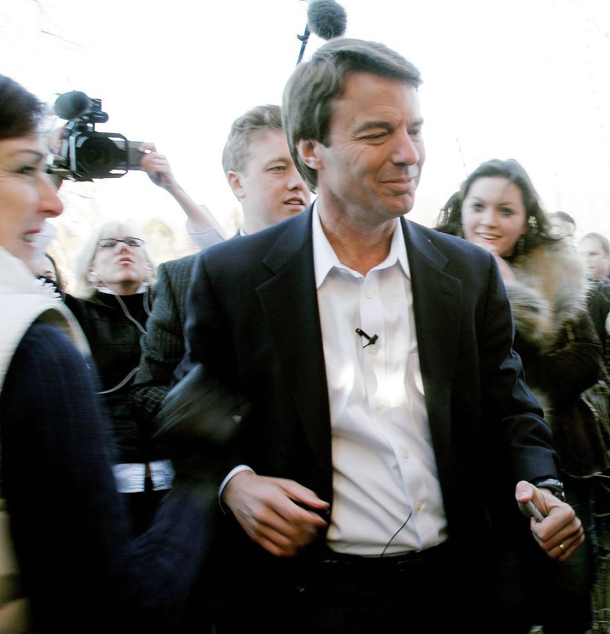 ** FILE ** Rielle Hunter (background left) holds a video camera as former Sen. John Edwards, North Carolina Democrat, campaigns for president in Portsmouth, N.H., in December 2006. Ms. Hunter had an affair and an out-of-wedlock child with Mr. Edwards. (AP Photo)