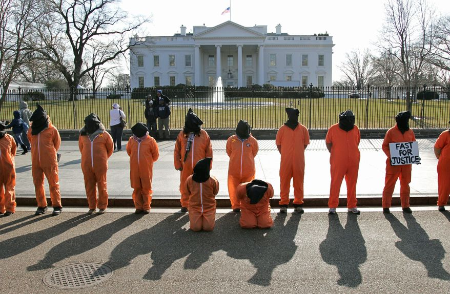 Human rights activists, wearing orange prison garb and black hoods to represent the prisoners at Guantanamo Bay, Cuba, stand on Pennsylvania Avenue outside the White House on Friday to protest that the detention center has not been closed by President Obama. (Associated Press)