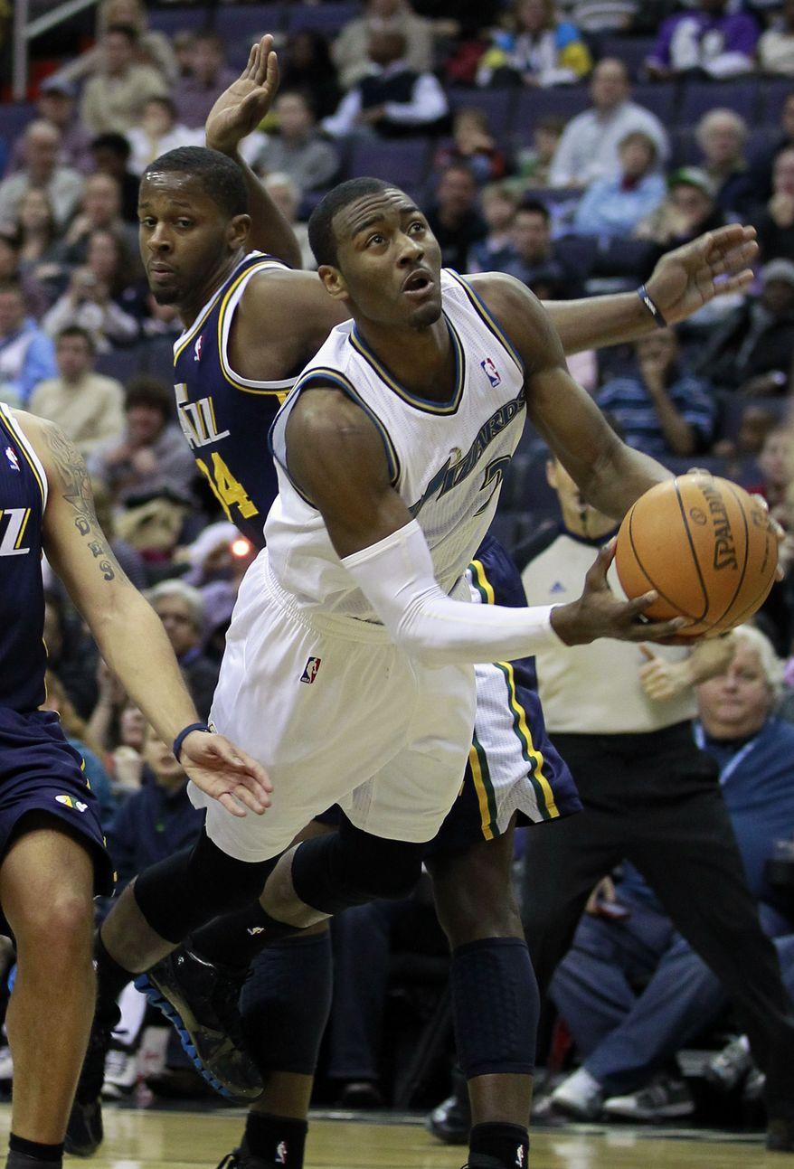 Utah Jazz forward C.J. Miles (34) tries to block Washington Wizards guard John Wall as he shoots in the first half of an NBA basketball game in Washington Monday, Jan. 17, 2011. (AP Photo/Alex Brandon)
