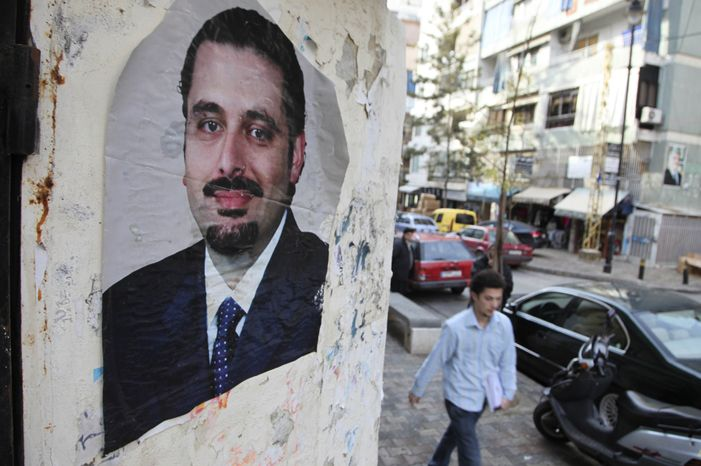 A man walks past a picture of Lebanese caretaker Prime Minister Saad Hariri in the Sunni neighborhood of Tarik Jdideh, in Beirut, Lebanon, Monday, Jan. 17, 2011. A U.N. tribunal filed the first indictment Monday in the assassination of former Lebanese Prime Minister Rafik Hariri. (AP Photo/Bilal Hussein)