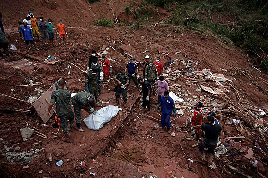 Rescue workers cover the recovered body of landslide victim Samara Coelho da Silva, 13, in Nova Friburgo, Brazil, Monday, Jan. 17, 2011. Brazil's army on Monday sent 700 soldiers to help throw a lifeline to desperate neighborhoods that have been cut off from food, water or help in recovering bodies since mudslides killed at least 642 people. (AP Photo/Felipe Dana)