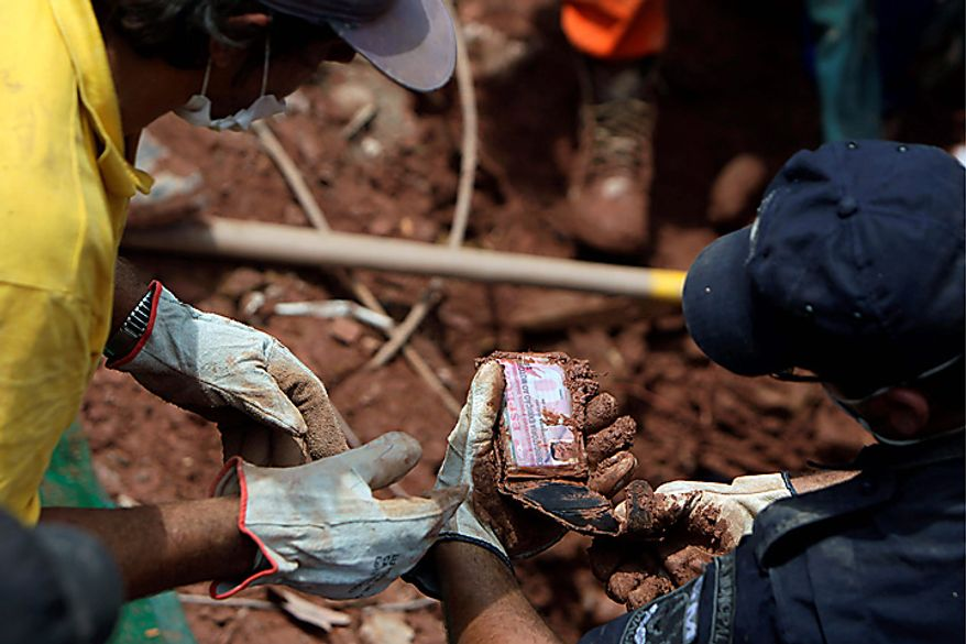 Rescue workers check the ID of Edilson da Silva found next to recovered bodies of landslides victims in Nova Friburgo, Brazil, Monday, Jan. 17, 2011. Brazil's army on Monday sent 700 soldiers to help throw a lifeline to desperate neighborhoods that have been cut off from food, water or help in recovering bodies since mudslides killed at least 642 people. (AP Photo/Felipe Dana)