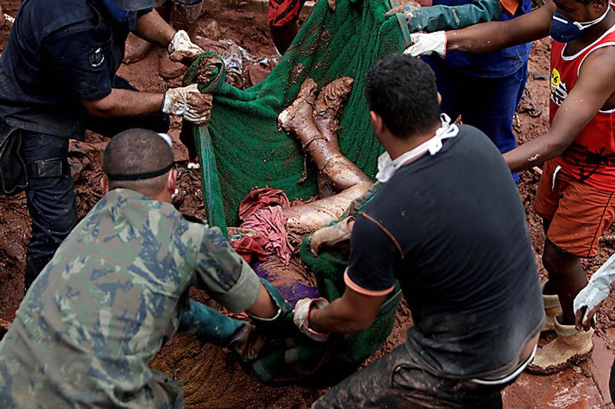 Rescue workers and residents recover the body of landslide victim Samara Coelho da Silva, 13, in Nova Friburgo, Brazil, Monday, Jan. 17, 2011. Brazil's army on Monday sent 700 soldiers to help throw a lifeline to desperate neighborhoods that have been cut off from food, water or help in recovering bodies since mudslides killed at least 642 people. (AP Photo/Felipe Dana)