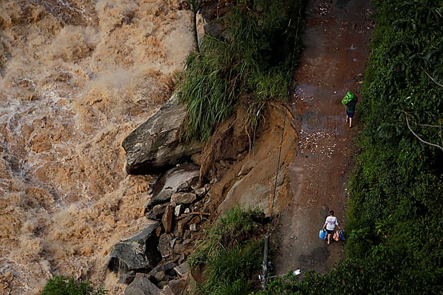 People leave their home at a flooded area after landslides in Nova Friburgo, Brazil, Monday, Jan. 17, 2011. (AP Photo/Felipe Dana)