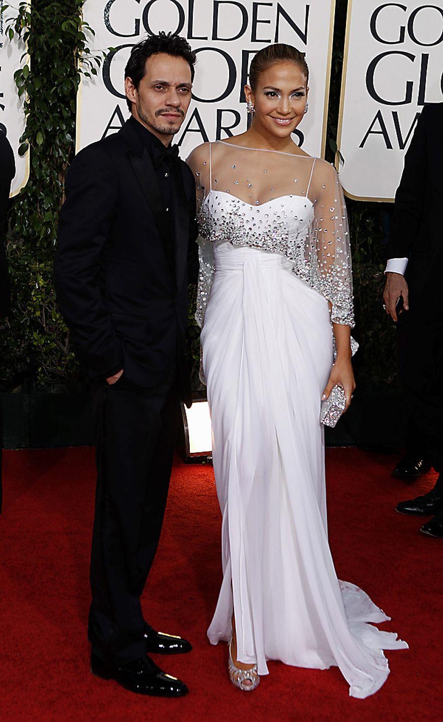 Jennifer Lopez arrives with her husband Marc Anthony, left, for the Golden Globe Awards Sunday, Jan. 16, 2011, in Beverly Hills, Calif. (AP Photo/Matt Sayles)