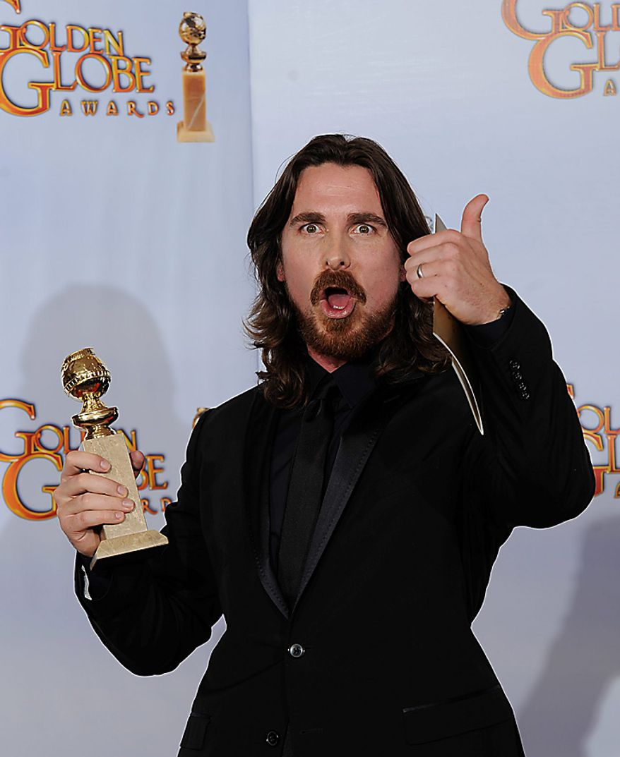 """Christian Bale holds up his trophy for Best Performance by an Actor in a Supporting Role in a Motion Picture for his role in """"The Fighter,"""" during the Golden Globe Awards Sunday, Jan. 16, 2011, in Beverly Hills, Calif. (AP Photo/Mark J. Terrill)"""