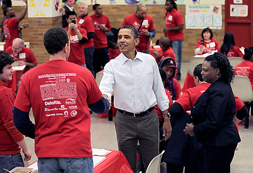 President Obama greets volunteers as he and first lady Michelle Obama observe the Martin Luther King Jr. Day holiday by participating in a community service project at the Stuart Hobson Middle School in Washington on Monday, Jan. 17, 2011. King, a preacher who rose to prominence as a leader of the black civil rights movement, was assassinated in 1968 in Memphis, Tenn. (AP Photo/J. Scott Applewhite)