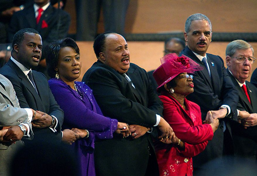 """Singing """"We Shall Overcome"""" during a service at Ebenezer Baptist Church honoring the 25th federal observance of Martin Luther King Jr. Day on Monday, Jan. 17, 2011, in Atlanta are (from left) Atlanta Mayor Kasim Reed; the Rev. Bernice King and Martin Luther King III, two of King's children; Christine King Farris, the late civil rights leader's sister; Attorney General Eric H. Holder Jr.; and Sen. Johnny Isakson, Georgia Republican. (AP Photo/David Goldman)"""