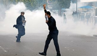 **FILE** Protesters run as riot police officers use tear gas during a demonstration in the center of Tunis on Jan. 18. (Associated Press)
