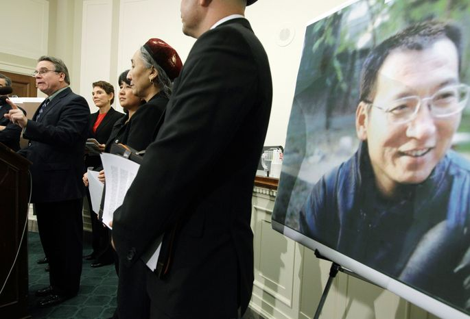 A poster of Liu Xiaobo, jailed Chinese activist and 2010 Nobel Peace Prize winner, is displayed as Rep. Christopher H. Smith, New Jersey Republican (left), speaks Tuesday on Capitol Hill about human-rights issues. (Associated Press)