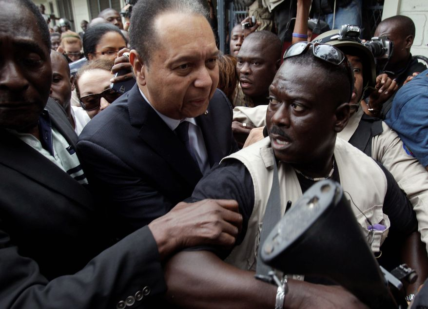 Haiti's ex-dictator Jean-Claude Duvalier (center) arrives to court surrounded by police in Port-au-Prince on Tuesday. Haitian police led him out of his hotel and took him to court Tuesday without saying whether he was being charged with crimes committed under his brutal regime. (Associated Press)