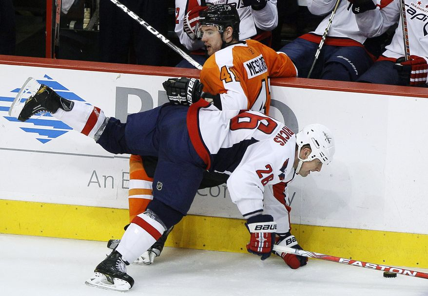 Washington Capitals' Matt Hendricks (26) collides with Philadelphia Flyers' Andrej Meszaros (41), sending Meszaros into the boards during the third period of the Flyers' 3-2 win in overtime on Tuesday. (Associated Press)