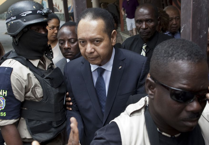 Police officers take ex-dictator Jean-Claude Duvalier out of his hotel in Port-au-Prince, Haiti, Tuesday Jan. 18, 2011. Haitian police took Mr. Duvalier, who abruptly returned to Haiti on Sunday, out of his hotel to a waiting SUV without saying whether he was being detained for crimes committed under his brutal regime. (AP Photo/Ramon Espinosa)