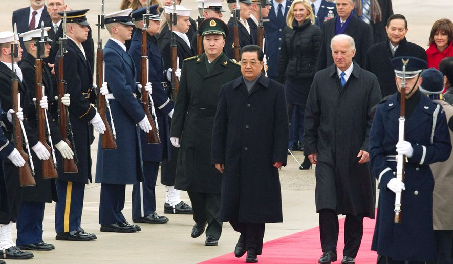 Chinese President Hu Jintao and Vice President Joseph R. Biden Jr. walk the red carpet upon Mr. Hu's arrival Tuesday at Andrews Air Force Base, Md., for the start of a state visit. China's trade with Iran will be one of many thorny issues President Obama will likely raise with Mr. Hu. (Associated Press)