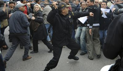 A police officer faces protesters during a demonstration against the Constitutional Democratic Rally, RCD, party of ousted President Zine El Abidine Ben Ali in the center of Tunis, Tuesday, Jan. 18. 2011. (AP Photo/Salah Habibi)