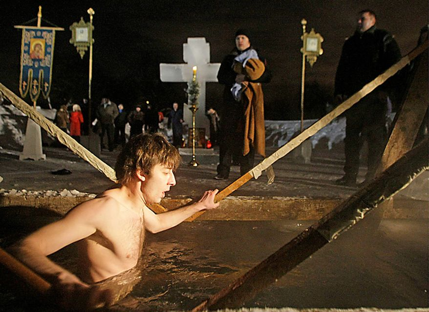 A man walks through the bath of the ice cold water in the ice hole of the pound in the Kolomenskoe park on the outskirts of Moscow, Russia, Wednesday, Jan. 19, 2011. Thousands of Russian Orthodox Church followers plunged Tuesday and Wednesday into icy rivers and ponds across the country to mark the upcoming Epiphany, cleansing themselves with water deemed holy for the day. Water that is blessed by a cleric on Epiphany is considered holy and pure until next year's celebration, and is believed to have special powers of protection and healing. The Russian Orthodox Church follows the old Julian calendar, according to which Epiphany falls on Jan. 19. Moscow temperatures on Wednesday night dropped to -14 C ( 7 F). (AP Photo/Mikhail Metzel)