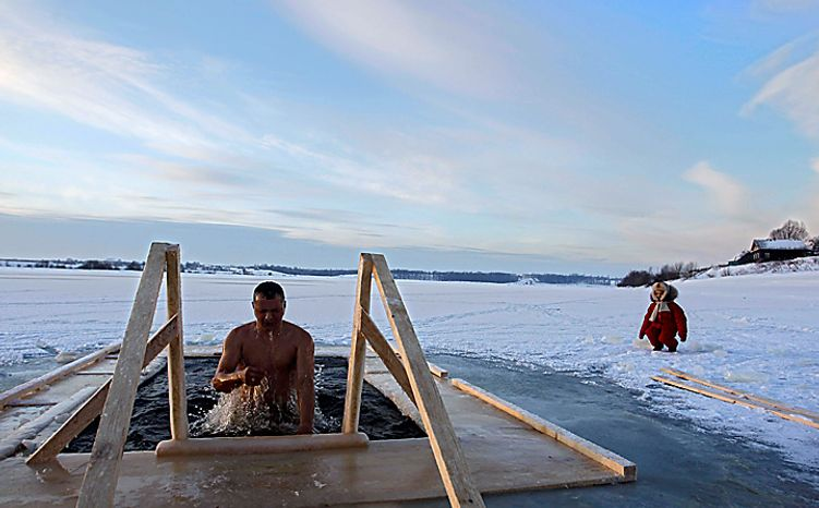 A Russian man emerges from cold water on Epiphany in Uglich, Russia, some 250 kilometers (150 miles) northeast from Moscow, Wednesday, Jan. 19, 2011. Thousands of Russian Orthodox Church followers plunged into icy rivers and ponds across the country to mark Epiphany, cleansing themselves with water deemed holy for the day. Water that is blessed by a cleric on Epiphany is considered holy and pure until next year's celebration, and is believed to have special powers of protection and healing. (AP Photo/Sergey Ponomarev)