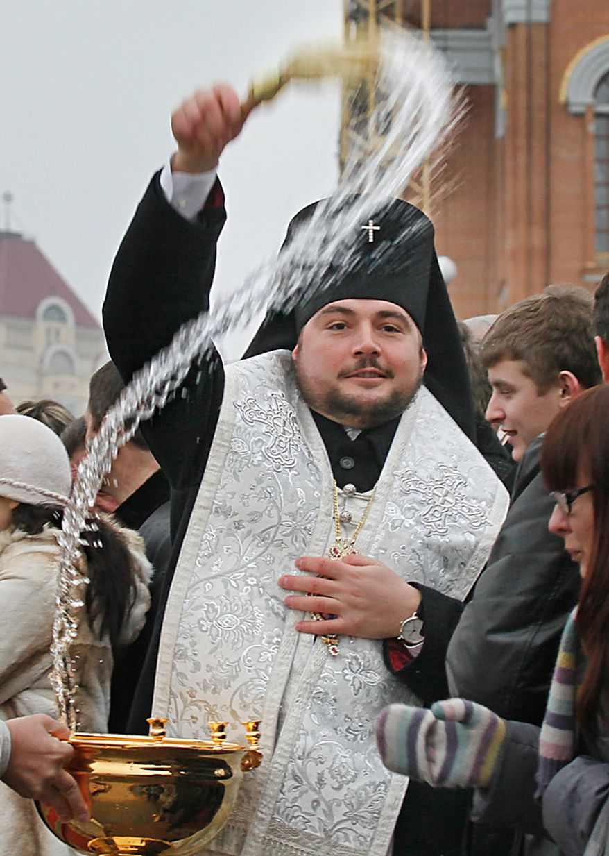 A Priest blesses Orthodox believers as part of celebrations of the Epiphany in Kiev, Ukraine, Wednesday, Jan. 19, 2011. Orthodox believers celebrate the holiday of the Epiphany on Jan. 19, and traditionally bathe in holes cut through ice on rivers and ponds to cleanse themselves with water deemed holy for the day as they commemorate Christ's baptism. (AP Photo/Efrem Lukatsky)