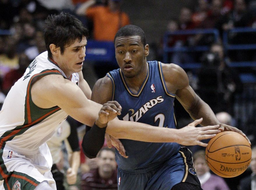 Washington Wizards' John Wall (2) is fouled as he tries to drive past Milwaukee Bucks' Ersan Ilyasova during the first half of an NBA basketball game Wednesday, Jan. 19, 2011, in Milwaukee. (AP Photo/Morry Gash)