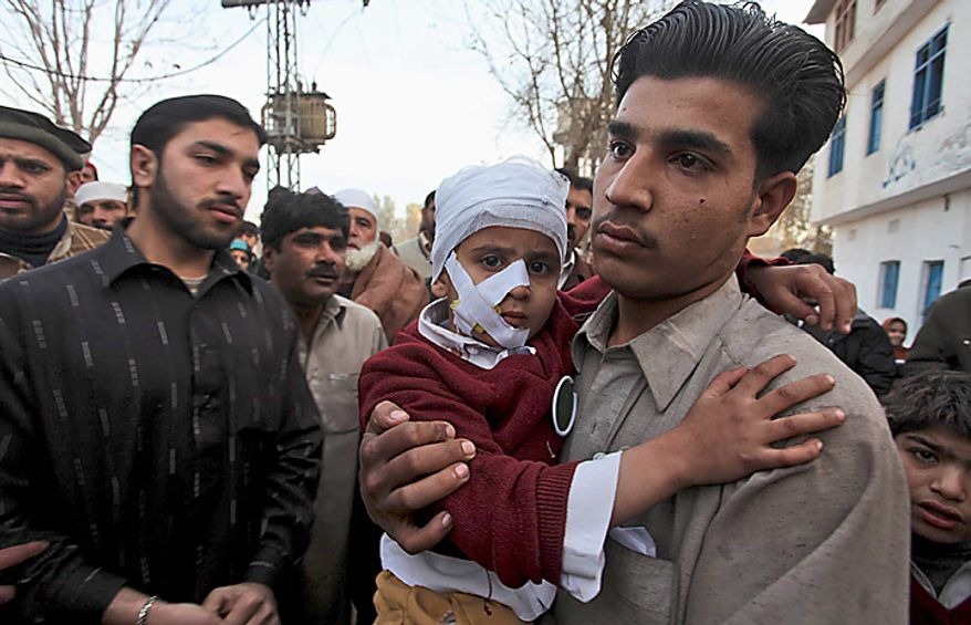 A man carries a wounded student at the site of a bomb explosion in Peshawar, Pakistan, Wednesday, Jan. 19, 2011. A bomb exploded outside a school in a residential area of Peshawar city on Wednesday, killing at least one person and wounding 14 others. (AP Photo/Mohammad Sajjad)