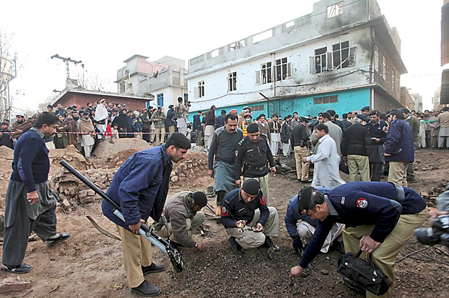 Police officers collect evidence from the site of a bomb explosion in Peshawar, Pakistan, Wednesday, Jan. 19, 2011.  A bomb exploded outside a school in a residential area of Peshawar city on Wednesday, killing at least one person and wounding 14 others. (AP Photo/Mohammad Sajjad)