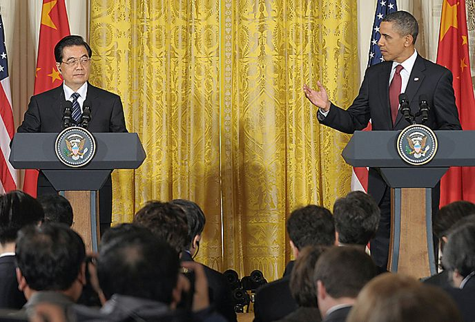 **FILE** President Obama gestures toward Chinese President Hu Jintao during a Jan. 19 news conference in the East Room of the White House. (Associated Press)