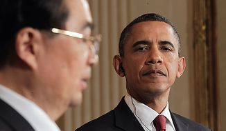 **FILE** President Obama looks on as Chinese President Hu Jintao speaks during a Jan. 19 news conference in the East Room of the White House. (Associated Press)