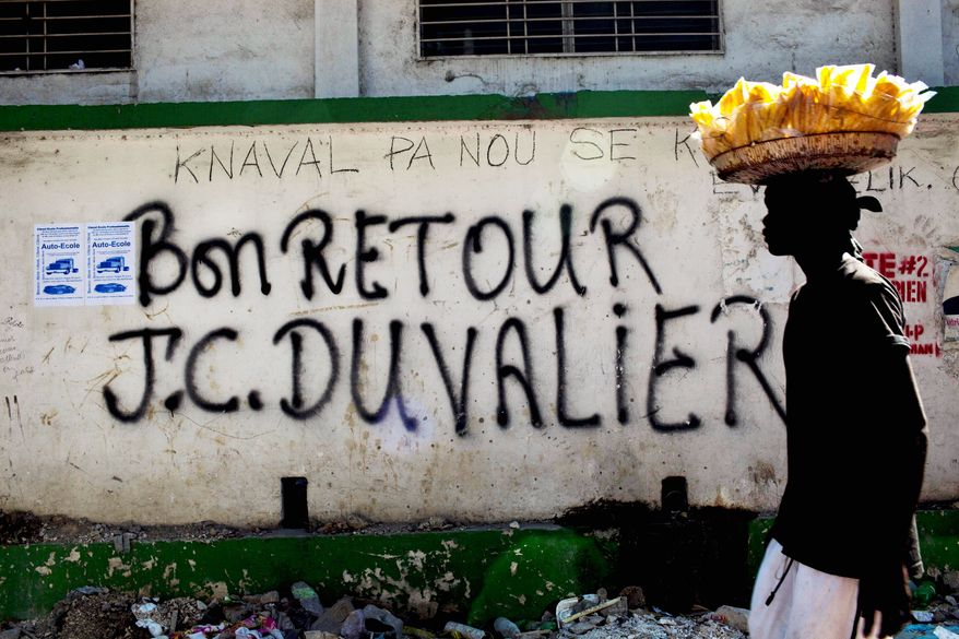 "A vendor walks past graffiti that reads in French ""Welcome back J.C. Duvalier"" in downtown Port-au-Prince on Thursday. Haiti's former dictator Jean-Claude Duvalier returned Sunday to Haiti after nearly 25 years in exile, a move that comes as his country struggles with a political crisis and the stalled effort to recover from last year's devastating earthquake. (Associated Press)"