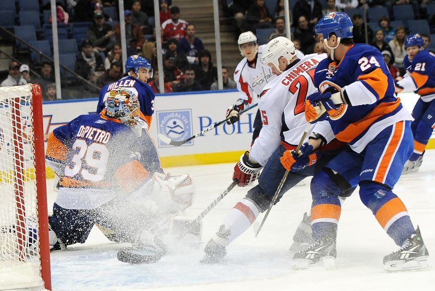 Washington Capitals' Jason Chimera (25) shoots the puck past New York Islanders goalie Rick DiPietro (39) to score as Islanders' Radek Martinek (24), of the Czech Republic, defends during the first period of an NHL hockey game Thursday, Jan. 20, 2011, in Uniondale, N.Y. (AP Photo/Kathy Kmonicek)