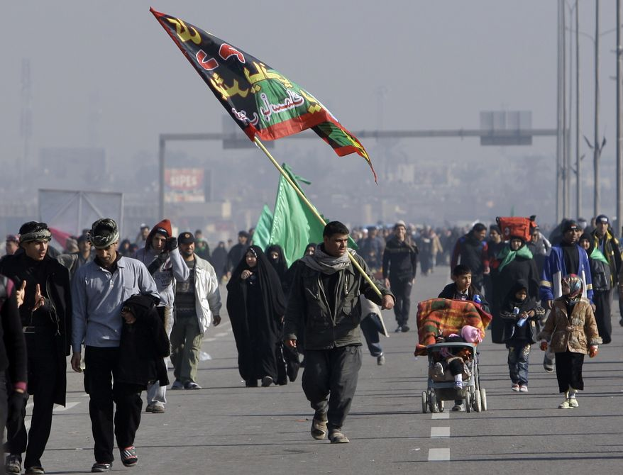 Shi'ite pilgrims march on their way to Karbala for Arbaeen, in Baghdad, Iraq, Thursday, Jan. 20, 2011. A pair of bombs blasted through security checkpoints ringing Karbala Thursday, Jan. 20, 2011,  and killed at least 50 people, many of whom were Shi'ite pilgrims headed to observe yearly religious rituals. (AP Photo/Khalid Mohammed)