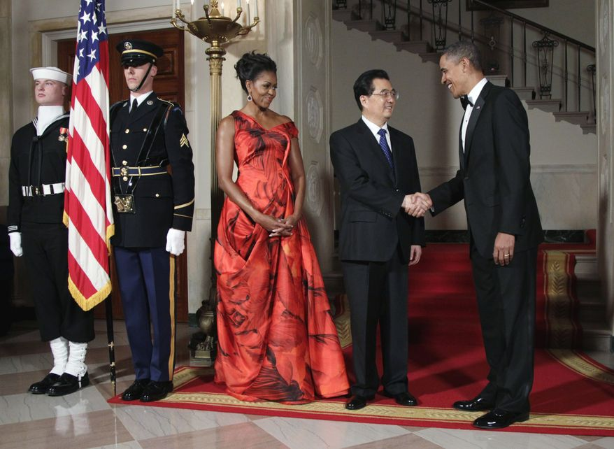 WELCOME: President Obama and first lady Michelle Obama greet Chinese President Hu Jintao on Wednesday before a state dinner for him. The leaders agreed to deals Mr. Obama said are worth $45 billion and 245,000 jobs to the U.S., but human rights and currency manipulation also came up. (Associated Press)