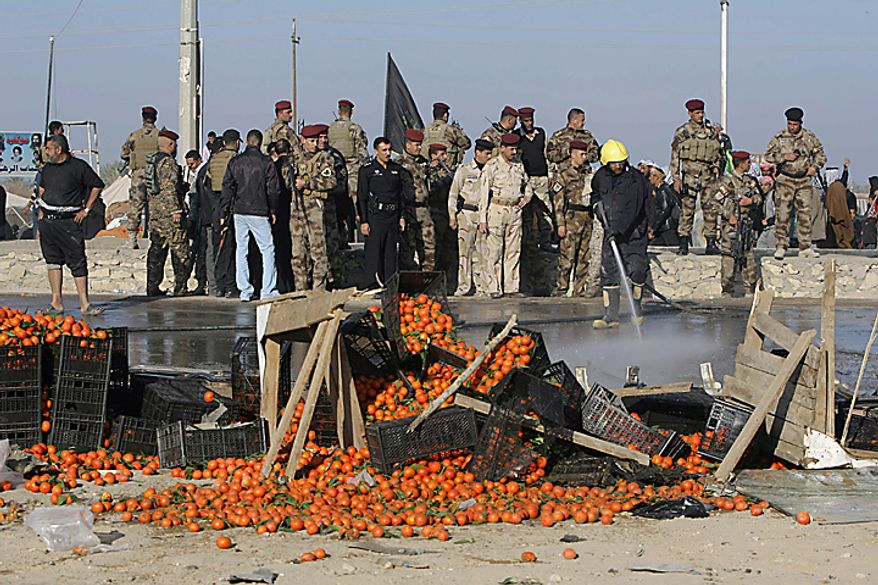 Iraqi security forces stand at the site of a bombing, that also upturned a fruit stand, in Karbala, 50 miles south of Baghdad, Iraq, Thursday, Jan. 20, 2011. A pair of bombs blasted through security checkpoints ringing the Iraqi holy city of Karbala Thursday and killed scores, most of whom were Shi'ite pilgrims headed to observe yearly religious rituals. (AP Photo/Ahmed al-Husseini)