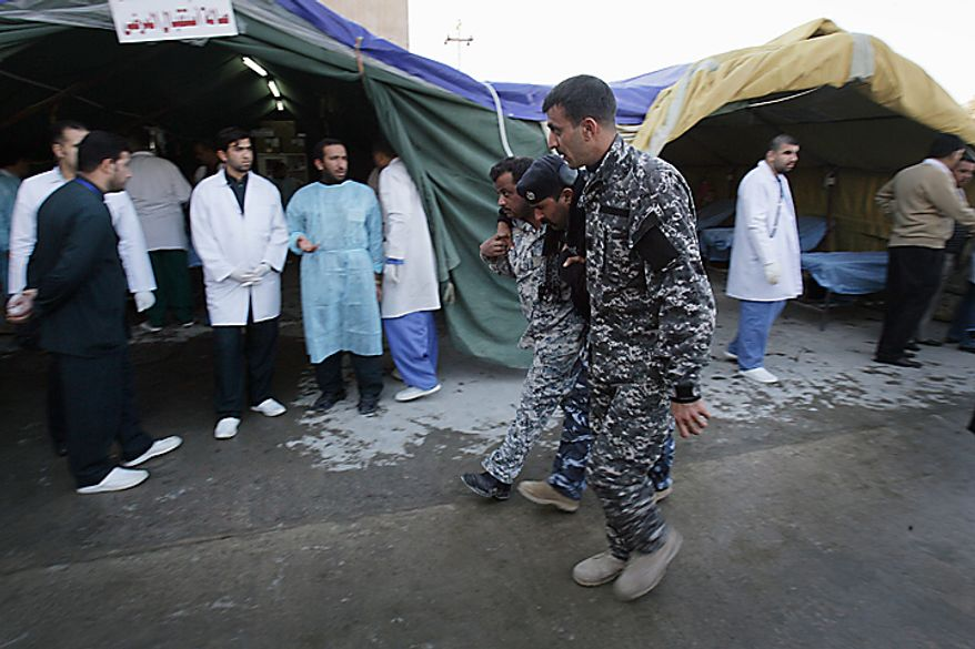 Iraqi police help a wounded comrade to safety in Karbala, 50 miles south of Baghdad, Iraq, Thursday, Jan. 20, 2011. A pair of bombs blasted through security checkpoints ringing the Iraqi holy city of Karbala Thursday and killed at scores, most of whom were Shi'ite pilgrims headed to observe yearly religious rituals. (AP Photo/Ahmed al-Husseini)