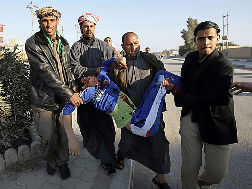 Men carry the body of a man killed in a bombing in Karbala, 50 miles south of Baghdad, Iraq, Thursday, Jan. 20, 2011. A pair of bombs blasted through security checkpoints ringing the Iraqi holy city of Karbala Thursday and killed scores of people, many of whom were Shi'ite pilgrims headed to observe yearly religious rituals. (AP Photo/Ahmed al-Husseini)