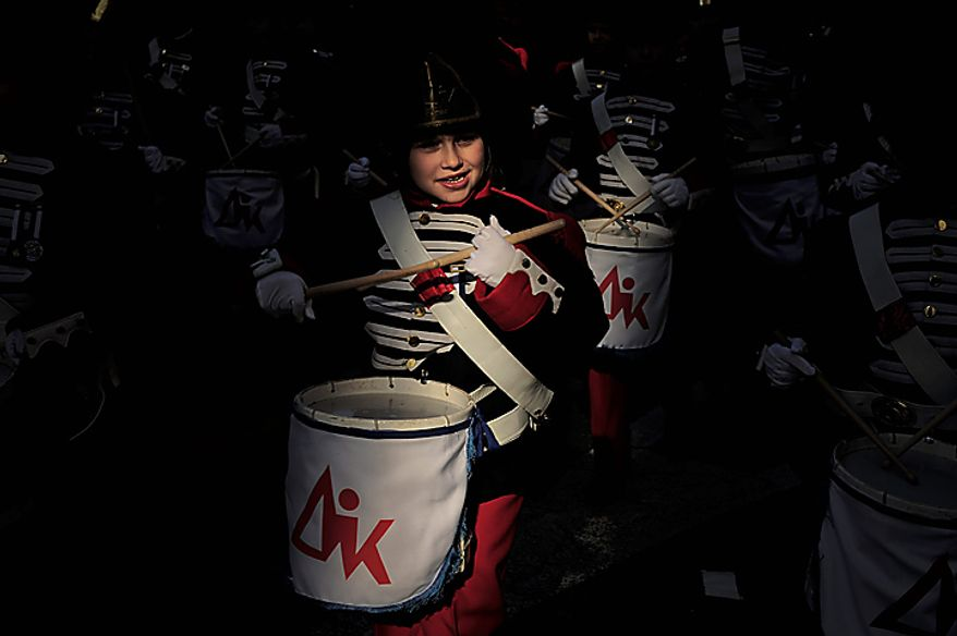 A Tamborillero wearing typical clothes participates in the traditional La Tamborrada during El Dia Grande, the main day of San Sebastian feasts, in the Basque city of San Sebastian, northern Spain, Thursday, Jan. 20, 2011. From midnight to midnight companies of perfectly uniformed marchers parade through the streets of San Sebastian playing drums and barrels in honor of their patron saint. (AP Photo/Alvaro Barrientos)