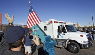People wave and applaud as the ambulance carrying Rep. Gabrielle Giffords leaves University Medical Center, Friday, Jan. 21, 2011, in Tucson, Ariz. Mrs. Giffords is being transported to a medical facility in Houston. (AP Photo/Matt York)