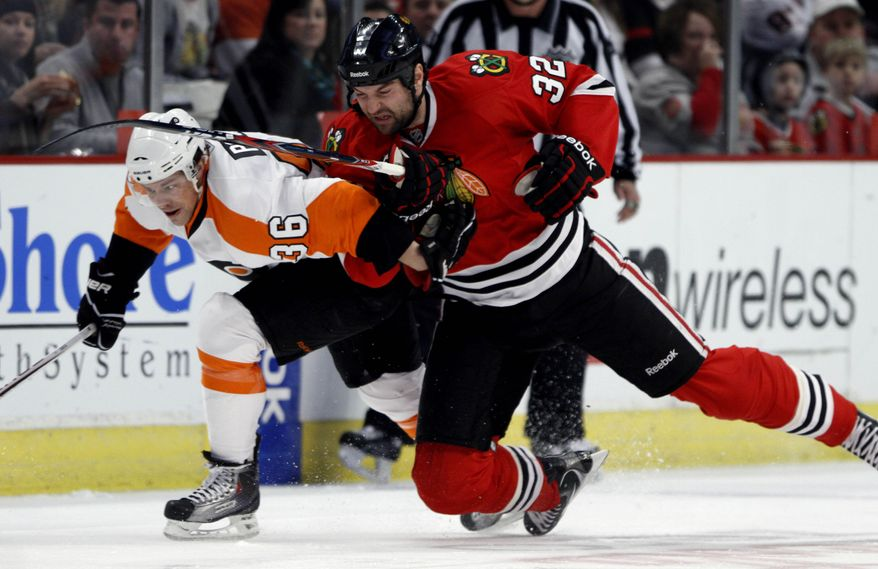Philadelphia Flyers' Darroll Powe, left, and Chicago Blackhawks' John Scott go after a loose puck during the first period in an NHL hockey game in Chicago on Sunday, Jan. 23, 2011. (AP Photo/Charles Cherney)