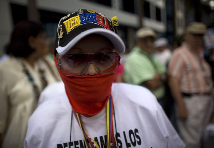A woman wears a gag during a demonstration Sunday in Caracas, Venezuela, marking a new anniversary of the overthrow of Venezuela's last dictator Gen. Marcos Perez Jimenez. Opposition supporters gathered along an avenue in eastern Caracas and chanted anti-government slogans while waving Venezuelan flags. (Associated Press)