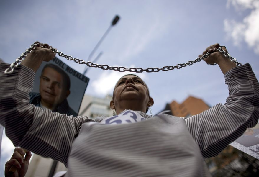 A woman dressed as a prisoner holds up chains during a demonstration Sunday in Caracas, Venezuela, marking a new anniversary of the overthrow of Venezuela's last dictator Gen. Marcos Perez Jimenez. Opposition supporters gathered along an avenue in eastern Caracas and chanted anti-government slogans while waving Venezuelan flags. (Associated Press)