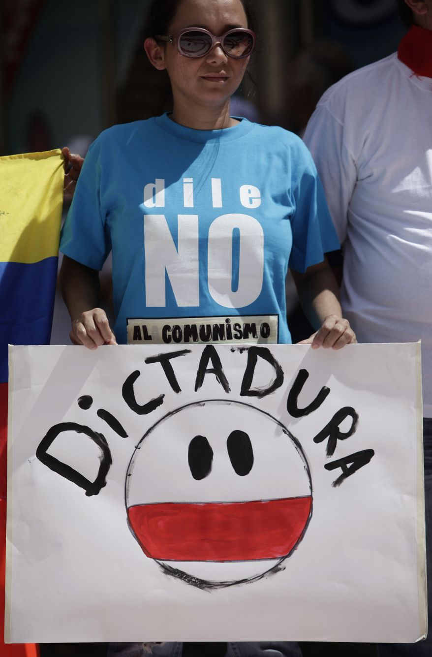 """A woman, wearing a T-shirt that reads in Spanish """"Say no to communism"""" and holding up a sign that reads in Spanish """"No more dictatorship,"""" looks on Sunday during a demonstration in Caracas, Venezuela, marking a new anniversary of the overthrow of Venezuela's last dictator Gen. Marcos Perez Jimenez. Opposition supporters gathered along an avenue in eastern Caracas and chanted anti-government slogans while waving Venezuelan flags. (Associated Press)"""