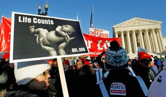 """Abortion foes gather Jan. 24 in front of the U.S. Supreme Court for a rally against the Roe v. Wade decision 38 years ago that legalized abortion. An estimated three dozen members of Congress spoke to the """"March for Life"""" crowd. (Associated Press)"""
