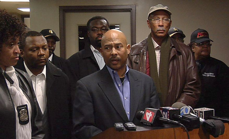 Detroit Police Chief Ralph Godbee (center) addresses the media at Sinai Grace Hospital, where police officers were taken after being shot by a gunman who walked into their precinct and opened fire. The gunman was killed after officers returned fire on Sunday, Jan. 23, 2011. Detroit Mayor Dave Bing (right) stands next to the police chief. (AP Photo/Detroit Free Press, Alexandra Bahou)
