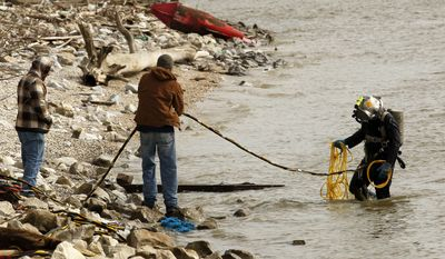 A diver emerges from the water while searching for the body of Brian Reed, the brother of Baltimore Ravens star Ed Reed in the Mississippi River in Kenner, La., Monday, Jan. 24, 2011. A man believed to be Brian Reed apparently jumped into the river on Jan. 7, after being confronted by a deputy sheriff. (AP Photo/Gerald Herbert)