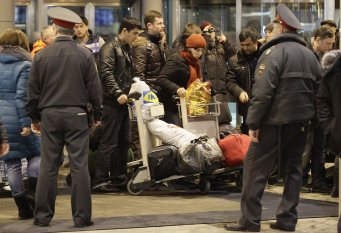 Police officers watch passengers at Domodedovo Airport in Moscow on Monday, Jan. 24, 2011, after an explosion ripped through the airport's arrivals hall. (AP Photo/Ivan Sekretarev)