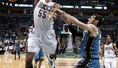 Milwaukee Bucks' Keyon Dooling (55) is fouled by Washington Wizards' Kirk Hinrich as he drives to the basket during the second half of an NBA basketball game Wednesday, Jan. 19, 2011, in Milwaukee. The Bucks won 100-87. (AP Photo/Morry Gash)